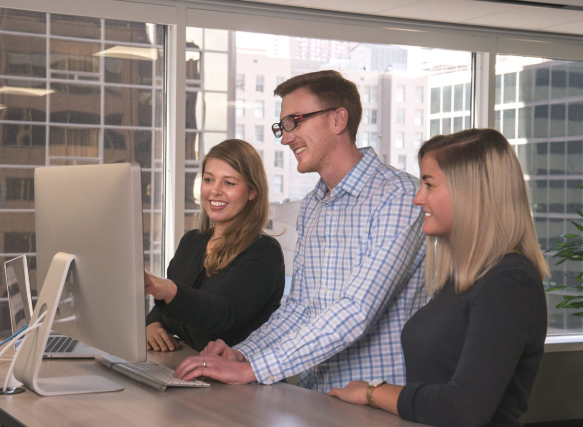 Three tech professionals in gathered around a desktop computer working together and smiling