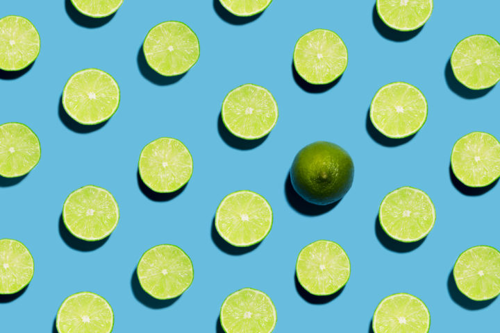 Sliced Open Geen Limes on Symmetrical Blue Background with one peeled open